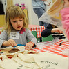 TIM JEAN/Staff photo<br /> Incoming kindergarten student Lilian Hoye adds glue as she makes a bear book bag during the Teddy Bear Picnic at the Golden Brook School in Windham. Students participated in crafts, meet teachers and even watched a puppet show.      5/5/16