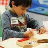 TIM JEAN/Staff photo<br /> Incoming kindergarten student Andrew Laher writes his name after making a bear book bag during the Teddy Bear Picnic at the Golden Brook School in Windham. Students participated in crafts, meet teachers and even watched a puppet show.      5/5/16