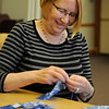 TIM JEAN/Staff photo<br /> Christine Surette of Windham, and a members of the Nesmith Quilters, works on section of a quilt the group is making at the Nesmith Library.        4/1/16