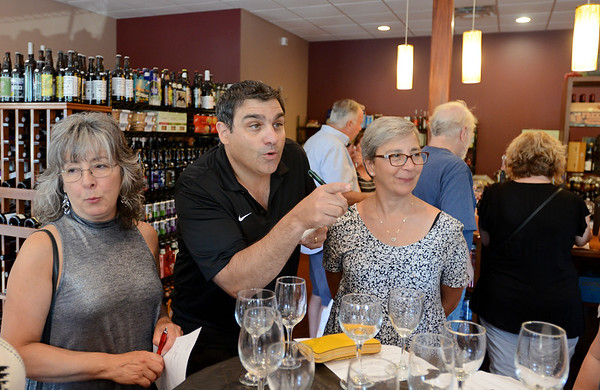 RYAN HUTTON/ Staff photo<br /> Chuck Palazzolo, owner of Lucia's Bodega, tallies up votes during a blind double wine tasting at his Windham shop.