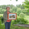 Joan Normington, Campbell Farm's longtime caretaker, poses with a photo she took of the multi-story barn that once existed in the backyard. AMANDA SABGA/ STAFF PHOTO<br /> <br /> The Campbell Farm house in Windham NH on June 26, 2015.