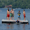 RYAN HUTTON/ Staff photo<br /> Children leap off the floating dock in the middle of Cobbetts Pond at Windham Beach on a hot Sunday in July.