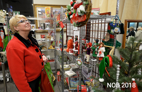 RYAN HUTTON/ Staff photo<br /> Linda Bushby checks out some of the Christmas merchandise available at the Beverly Bootstraps Thrift Shop's fundraising event on December 7.