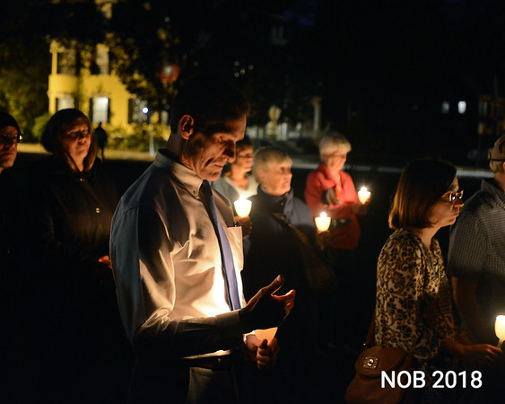 RYAN HUTTON/ Staff photo<br /> Beverly Mayor Michael Cahill joins a few dozen people gathered on the Beverly Common on Tuesday night for a candlelight vigil put on by the Beverly Multifaith Coalition for the recent mass shooting in Las Vegas.