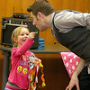 Elyse Fox, 3, from Lunenburg helps magician Todd Migliacci with his magic trick as she pulls some streamers from his mouth on Tuesday February 21, 2017 at the Leominster Library. SENTINEL & ENTERPRISE/JOHN LOVE