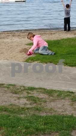 Baylee Willson enjoys her weekend by playing in the sand next to the beach at Triggs Resort in Okoboji.