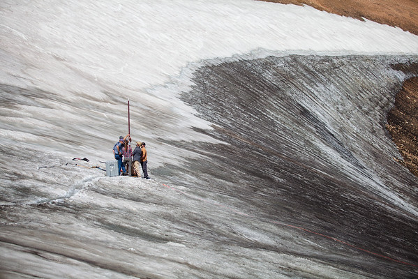 Members of an archaeological and climate science research team extract a deep ice core from an ice patch in northern Wyoming