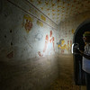A Nubian guide shines a light at a wall in a subterranean Egyptian tomb at El Kurru