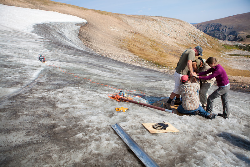Researchers put heavy weight on a drill to extract an alpine ice core