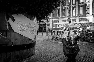 Two young women taking selfies, Covent Garden, London