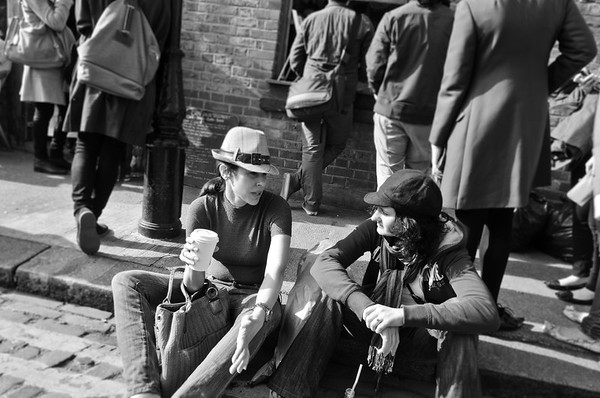 Two young fashion conscious women sitting on the pavement and talking to each other in Columbia Road, East London