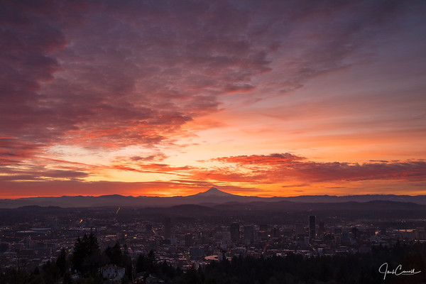 The sun rising over Mt. Hood and downtown Portland as seen from the Pittock Mansion.