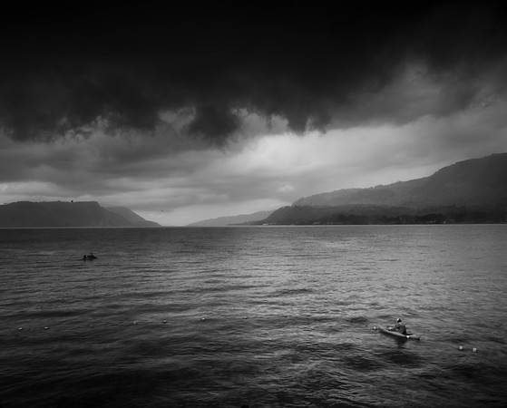A Batak fisherman braves a storm to check his nets on Lake Toba near Samosir Island