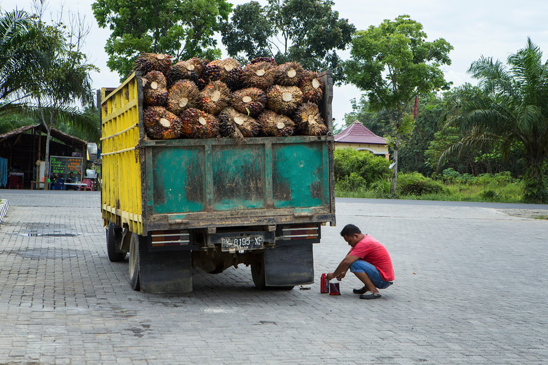 A truck carrying palm nuts is repaired at a gas station
