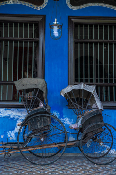 Covered rickshaws outside of the Cheong Fatt Tze Blue Mansion hotel in UNESCO. The Blue Mansion was originally home of 19th century architect Cheong Fatt Tze and is only one of two mansions in this size and style to exist outside of China. It was only recently turned into a luxury boutique hotel in 1995.