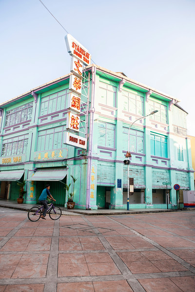 A man rides his bike past a classic example of Peranekan architecture in George Town, Malaysia.