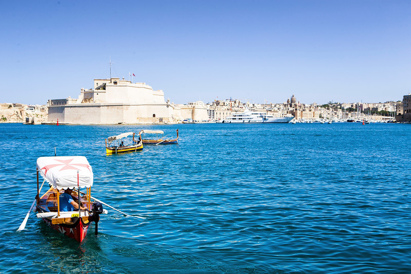 A group of historic wooden boats operate as taxis to shuttle tourists across the bay of Valletta to the Three Cities, Malta