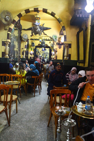 Tourists and locals enjoy tea and water pipes at El Fishawi's, the longest running coffee house in the world. Cairo, Egypt