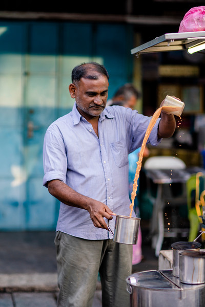 A tea vendor makes teh tarik, or pulled tea, the national drink of Malaysia. Teh Tarik is a mix of strong black tea, sugar, and condensed milk which is 'pulled' through the air to aerate and froth the drink. First introduced to Malaysia by south Indian immigrants offering cheap food to Chinese miners, teh tarik is now a symbol and staple of Malaysian culture