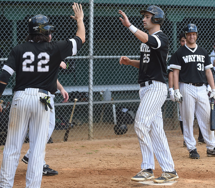 . PETE BANNAN-DIGITAL FIRST MEDIA        Chris Cowell is congratulated at home by #22 Dan WIlliams after Cowell hit a grandslam in the bottom of the sixth inning to power Wayne over Narberth 6-4 in game three of the Delco League playoff championship series at Radnor High School Sunday.