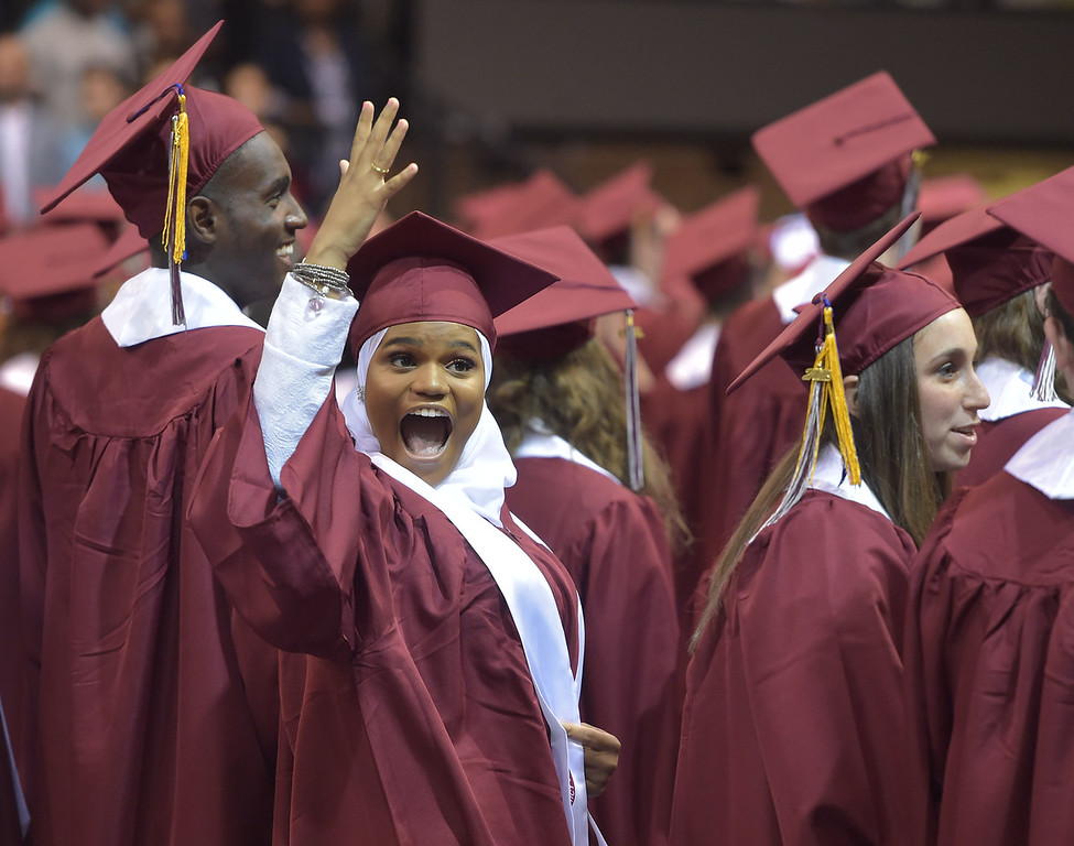 . PETE  BANNAN-DIGITAL FIRST MEDIA           Lower Merion senior Suhailah Rashid-Woods signals to family members during graduation Wednesday evening at Hagan Arena St. Joseph\'s University.