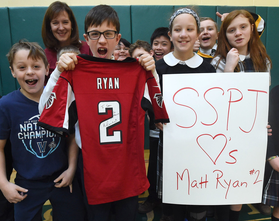 . PETE  BANNAN-DIGITAL FIRST MEDIA    Fourth grader, Sam Conte holds up his autographed Matt Ryan Atlanta Falcons jersey at the Super Bowl of Caring rally at SS. Philip & James School in Exton Monday.  The rally was part of the school\'s kick-off of Catholic School\'s Week.  Matt Ryan graduated from the school in 1999. Students brought in cans goods for area poor as part of the program.