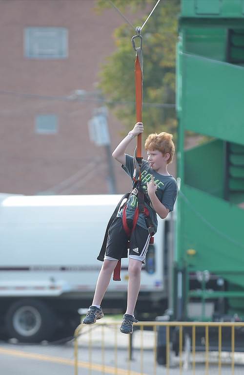 . PETE  BANNAN-DIGITAL FIRST MEDIA   Bobby Potts of Upper Darby enjoys the zipline at the Wayne Fall Festival Sunday. Streets and lots along N. Wayne and West Ave. were closed to enjoy the 25th annual festival.