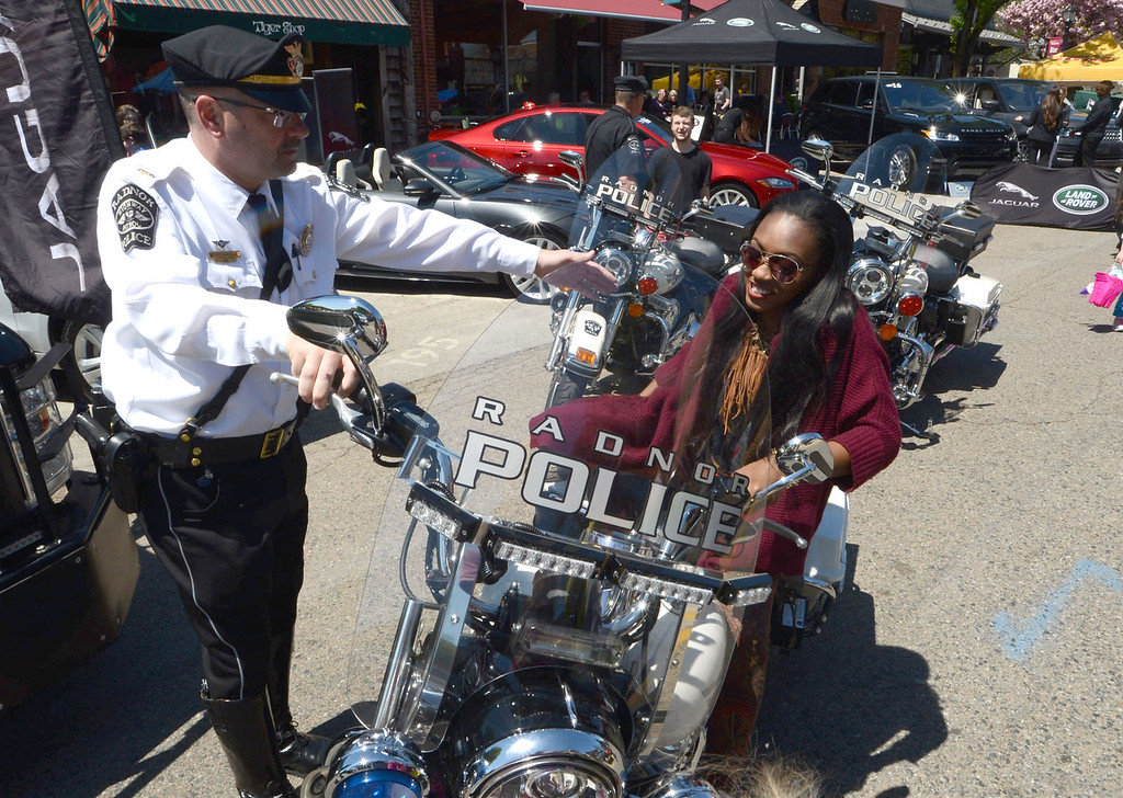 . PETE BANNAN-DIGITAL FIRST MEDIA   Shanell Campbell of Phila. tests out Radnor police Lt. Chris Flanagan\'s Harley Davidson  motorcycle as antique and classic cars lined N. Wayne and West Aves. in Wayne Sunday as the fourth annual Wheels of Wayne car and motorcycle show brought Porsches, Mustangs, even the Wienermoblie to town.