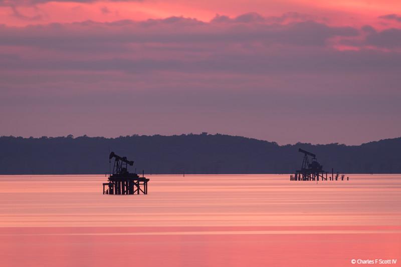 Caddo Lake oil derricks at sunset