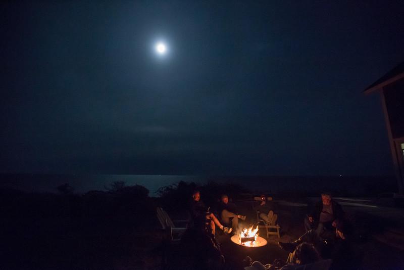 Friday night fire under hazy moon.