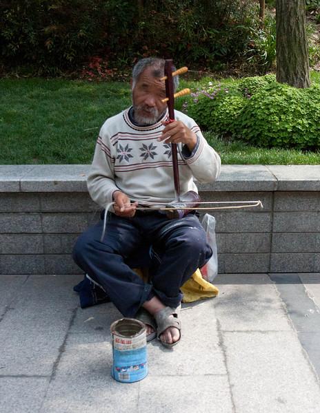 Street beggar playing local instrument.