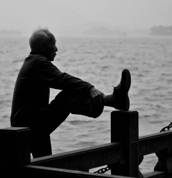 Old man stretching Saturday morning along West Lake.