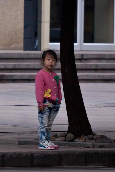 Girl waiting to cross the street in HangZhou.