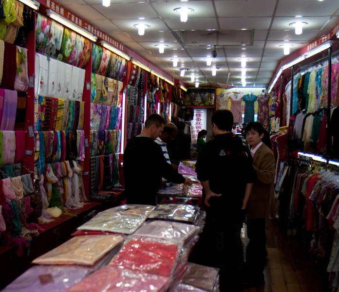 Frank and Kuna bargaining in silk store .