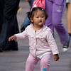 young girl dances in the crowded shopping district.