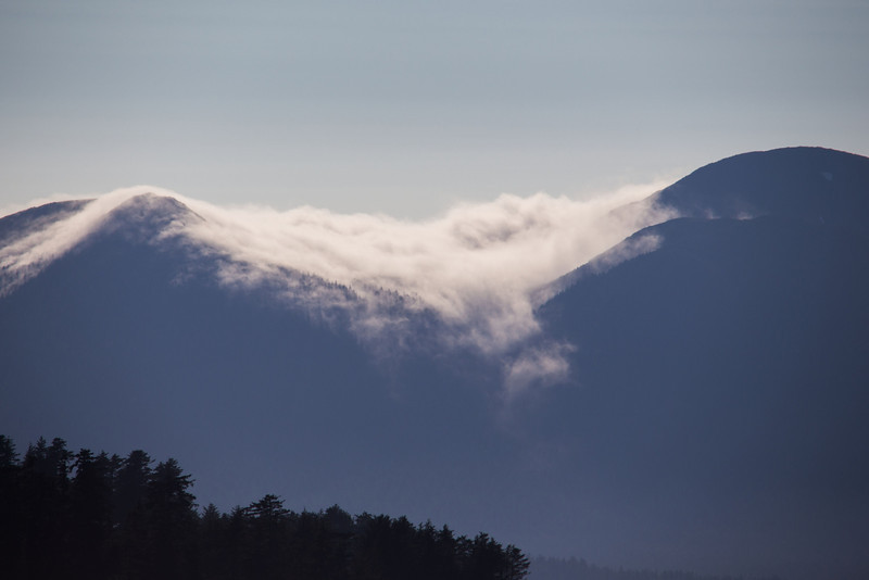 clouds spilling over the top of a volcano.