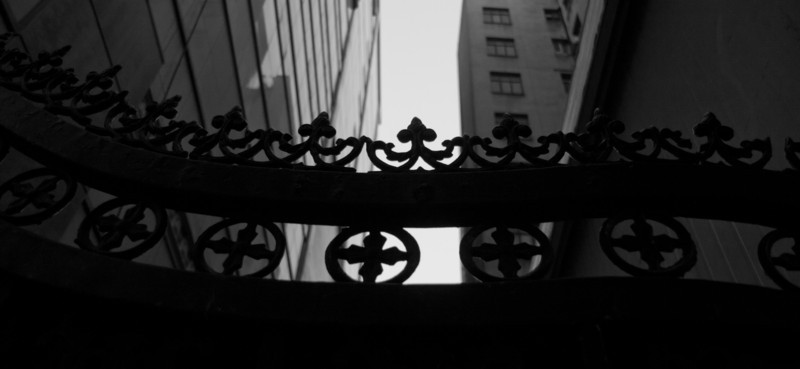 Old Iron gate in front of modern sky scrapers.