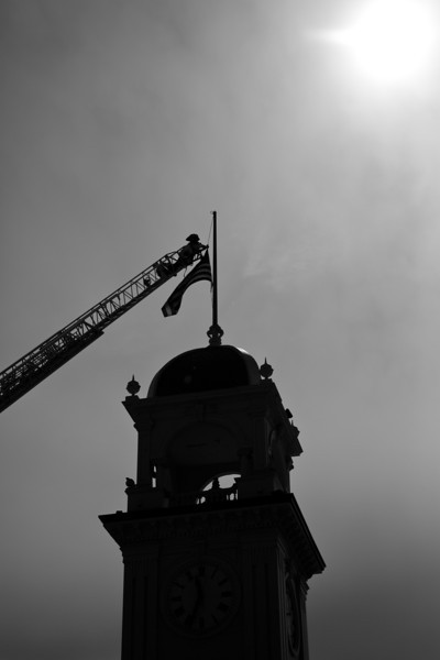 On Tuesday February 26th two SCPD officers where killed.  This photo shows a Santa Cruz firefighter lowering the flag flying above the town clock to half mast.