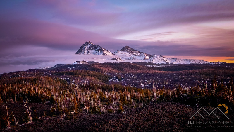 North and Middle Sister hugged by clouds at sunset from McKenzie Pass.