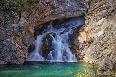 Running Eagle Falls or Trick Falls During high water, there are two falls. The water leaps from the top shelf, hiding a second hidden falls that roars out of a cave half way down. At lower flows like this day, water only gushes out from the cave leaving the top dry.
