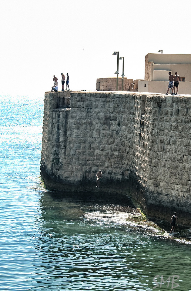 Boys jumping off the seawalls of the old city of Acre, Israel