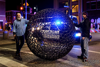Some artists and the metal sphere sculpture, on Congress St during the First Friday Art Walk