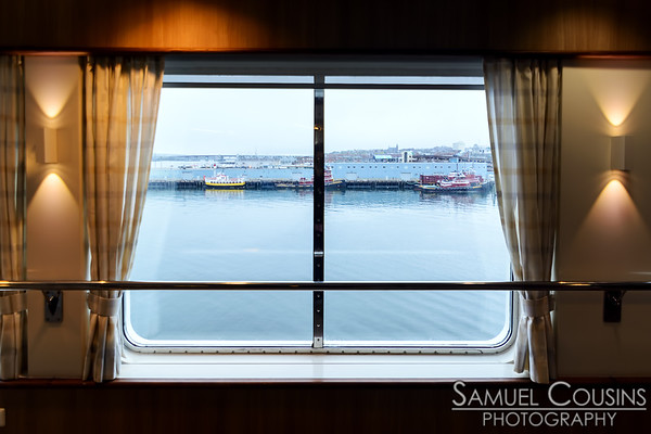 Looking out a window of the Nova Star at boats docks at the Maine State Pier.