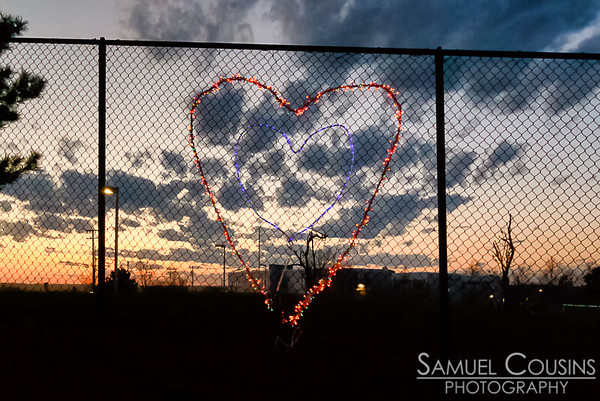 Lights in the shape of a heart, on the fence around the field of the East End School