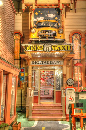 In a small alley in downtown Bar Harbor, Maine sits the unique restaurant called Dink's Taxi.  Half of a taxi sits over the restaurant entrance.  Pretty cool place with Route 66 signs, gas pumps, and street lights.