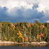 Fall foliage and brooding clouds looking from West Point across Totman Cove to Bailey Point, Phippsburg,  Maine autumn