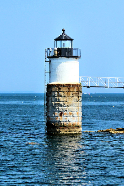 A 35 foot cylindrical tower was erected on a rock outcropping just offshore.  The structure consisted of a granite base with a brick tower.  The tower was topped with a cast iron lantern housing a fixed 4th Order Fresnel lens.  A walkway was built atop iron piers reaching 214 feet from the lighthouse to the island.