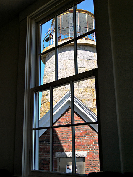 **Looking at the lighthouse tower from the bedroom on the second floor.**  The keeper could keep an eye on the light throughout the night while lying in his bed. In 1982 the light was automated and the keepers removed. The Third Order lens was replaced with a green 300mm optic. The lens is now on display at the Maine Lighthouse Museum in Rockland. The light was converted to solar power in 2001.