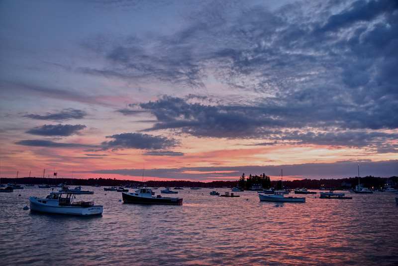"Boothbay Harbor, Maine, August 21, 2011, 7:47 pm <br><br> Boothbay Harbor, Maine (population 2,300) is located on the central coast of Maine and is a popular tourist destination. My wife's family has been vacationing there for over 40 years. I am a relative newcomer, having been to Boothbay for the past 10 years. Boothbay is filled with quaint places; my favorites include Down East Ice Cream Factory, Brown's Warf Restaurant, Fudge Factory, Romar candlepin bowling, and Thursday evening band concerts on the library lawn. In short, a perfect New England destination for a summer vacation. <br><br> This was taken from a memorial overlooking the harbor that is a great place to view stunning sunsets. Our Lady Queen of Peace church donated a parcel of land to the Fisherman's Memorial Committee in 1983. The committee created a bronze fishing dory (small boat) dedicated to the memory of the over 229 fishermen from the Boothbay Region who were lost at sea during the last two centuries. For a live view of the harbor, take a look at the <a href=""http://www.brownswharfinn.com/bw_camera.html"">Brown's Warf Restaurant webcam</a>."