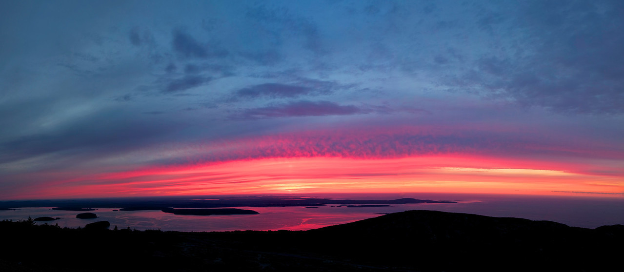 """Sunrise from Cadillac Mountain, Acadia National  Park, Maine, August 26, 2013, 5:37 a.m.  <br><br> While vacationing in Boothbay Harbor, Maine, our family took a 2-day trip to Acadia National Park, 130 mies north. When checking in to our motel at Bar Harbor, the woman at the front desk assured me that Cadillac Mountain is the place to be for great sunrises. After checking out the mountain that afternoon with it's spectacular sweeping views, it seemed like a good plan and hoped for nice clouds the next morning.  <br><br> The forecast for the next morning was for overcast skies and rain, generally not conducive to landscape photography. I peaked out the window at 4:30 a.m. and saw a glimmer of hope: although the sky was generally overcast, there were a few large horizontal splits in the clouds. If the openings in the clouds held up, the sunrays would bounce off the upper and lower clouds, creating the possibility of a great sunrise.  <br><br> I drove up the winding Cadillac Mountain for about 20 minutes, reaching the summit at about 5:30 a.m. There were dozens of people at the summit as catching the first sunrise in the U.S. is popular among Acadia National Park visitors (actually, the first sunrise in the U.S. can be seen from Cadillac Mountain only in the fall and winter when the sun rises south of due east). As the photo indicates, the sunrise that morning was stunning, with an explosion of blue and orange colors as the sunrays bounced against the clouds. This photo provides a sweeping view of the sunrise, with Bar Harbor as the backdrop-a very special and memorable moment that was the highlight of our trip. Not much post-production work on this photo, as I couldn't improve on the spectacular show that Mother Nature put on that morning. <br><br> Cadillac Mountain is within Acadia National Park with an elevation of about 1,500 feet, according to <a href=""""http://en.wikipedia.org/wiki/Cadillac_Mountain"""">Wikipedia</a>. The mountain honors the French explorer and advent"""